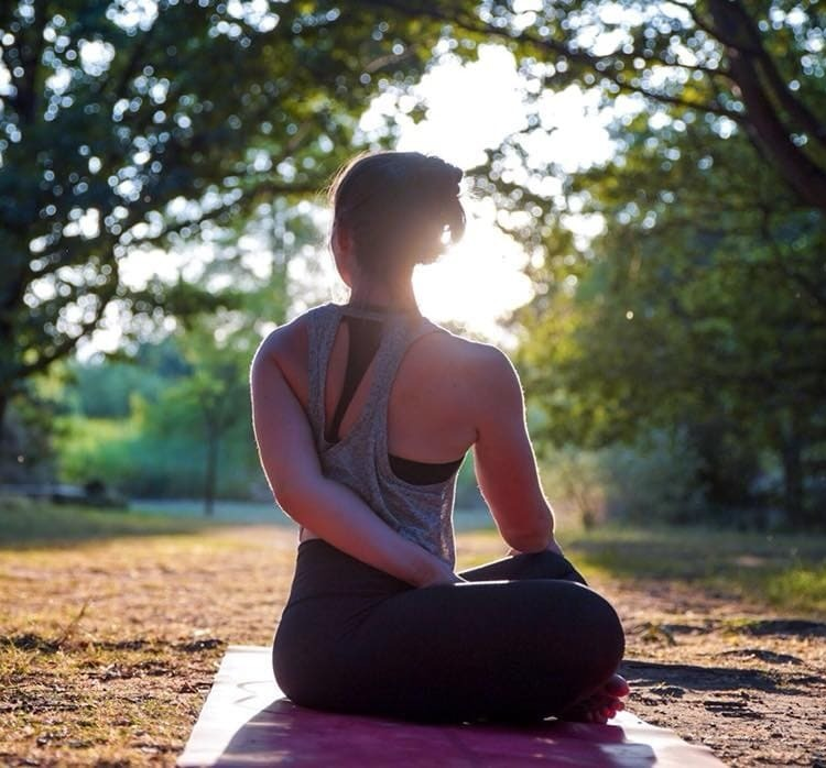 Woman on yoga mat at the park - Yoga Winchester